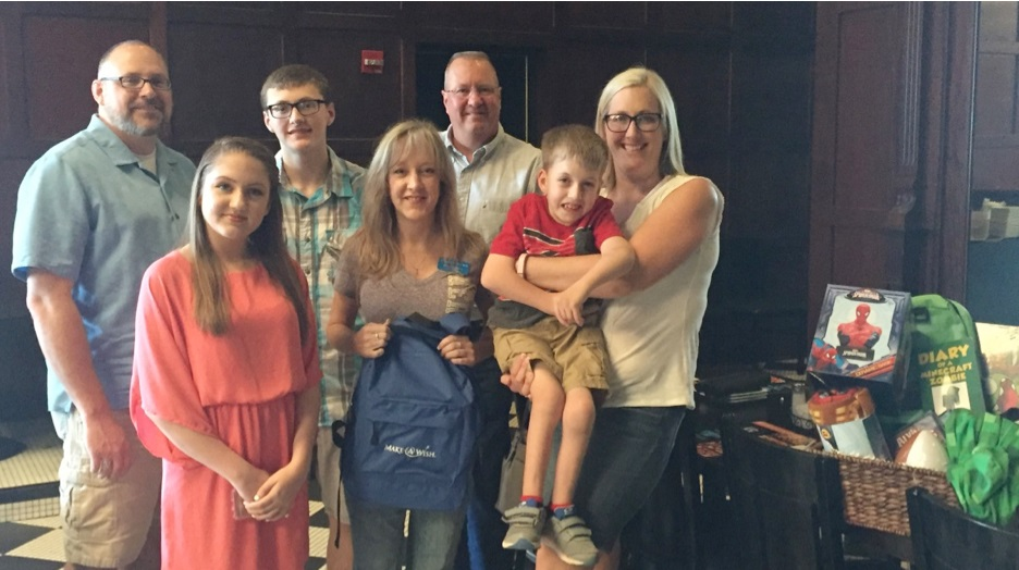 Gary Rose (right, back row), director of operations, Texas Utilities for SouthWest Water Company, poses with Owen and his family, as well as representatives from Make-A-Wish.