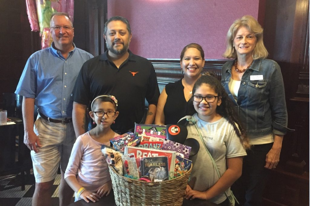 Gary Rose (left, back row), director of operations, Texas Utilities for SouthWest Water Company, poses with Alixandra and her family, as well as a representative from Make-A-Wish.